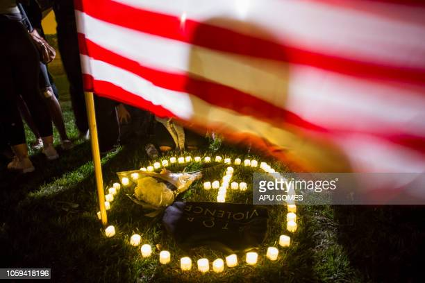 People stand next to candles during a vigil to pay tribute to the victims of a shooting in Thousand Oaks California on November 8 2018 A 28yearold US...