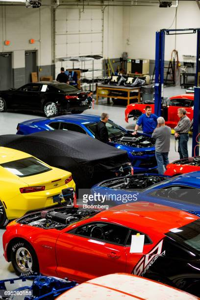 People stand next to completed and nearly completed General Motors Co Chevrolet COPO Camaro performance vehicles at the company's build center in...