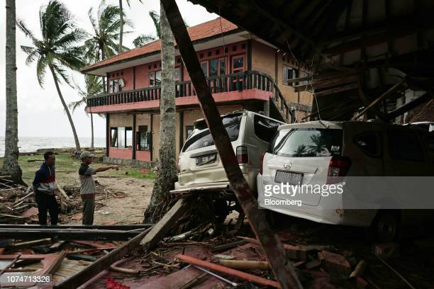 People stand next to damaged vehicles at the Villa Avi Redita in Carita Banten province Indonesia on Monday Dec 24 2018 Rescuers hunted for survivors...