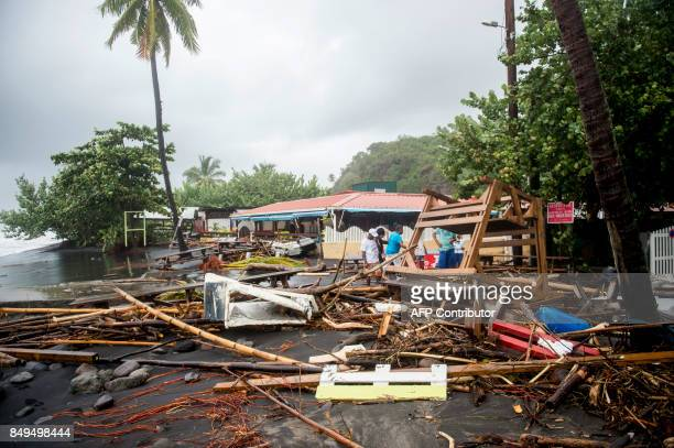 People stand next to debris at a restaurant in Le Carbet, on the French Caribbean island of Martinique, after it was hit by Hurricane Maria, on...