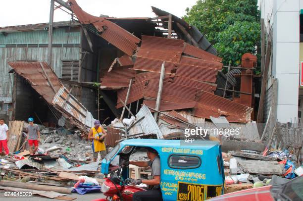People stand next to debris from a collapsed house after a 6.8-magnitude earthquake hit General Santos City, in southern island of Mindanao on April...