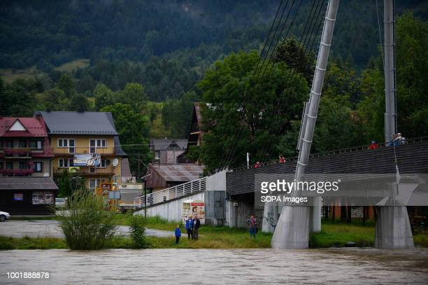 People stand next to Dunajec River during a flood alert due to the extreme rain falls Southern Poland and northern Slovakia on flood alert due to...