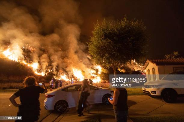 TOPSHOT People stand next to flames rising from the Ranch fire in the San Gabriel mountains above Azusa 25 miles east of Los Angeles California on...