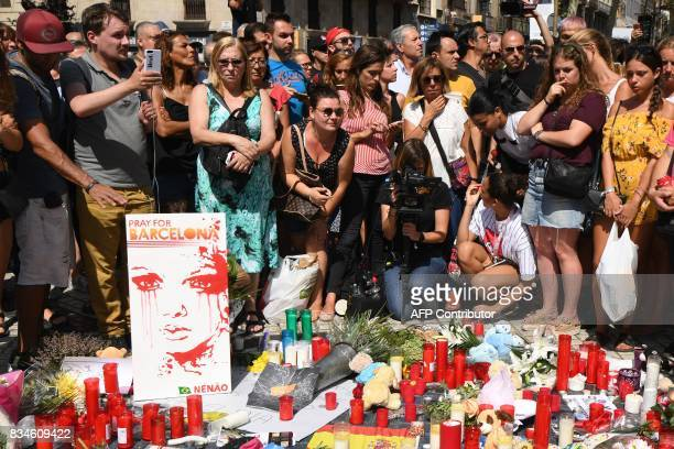 TOPSHOT People stand next to flowers candles a poster reading 'Pray for Barcelona' and other items set up on the Las Ramblas boulevard in Barcelona...