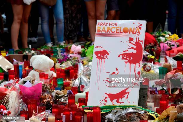 TOPSHOT People stand next to flowers candles and other items set up on the Las Ramblas boulevard in Barcelona as they pay tribute to the victims of...