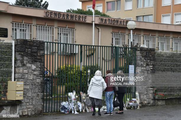 TOPSHOT People stand next to flowers laid in front of the Gendarmerie Nationale in Carcassonne on March 24 2018 in tribute to the gendarme killed...