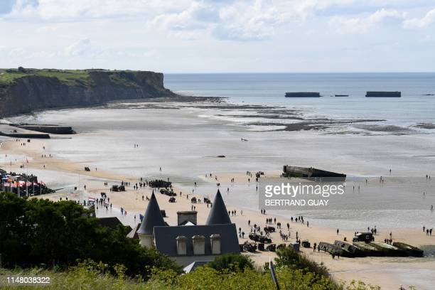 TOPSHOT People stand next to military vehicles from the WWII at the beach in Arromancheslesbains northern France on June 4 ahead of DDay 75th...