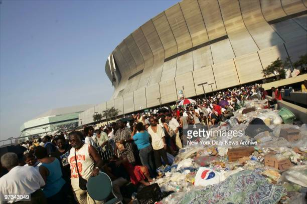 People stand next to piles of garbage outside the Superdome in New Orleans as they wait to be evacuated from the city in the wake of Hurricane...