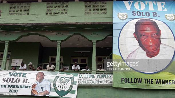 People stand next to posters showing Presidential candidate Vice President Solomon Berewa from the ruling Sierra Leone People's Party in Bo 07...