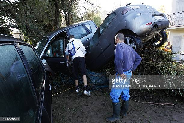 People stand next to rubble and damaged cars after violent storms and floods in Biot southeastern France on October 4 2015 Violent floods along the...