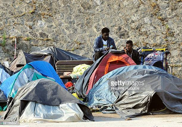 People stand next to tents set up by migrants on a bank in Calais western France on May 18 2014 As border controls have relaxed across Europe the...