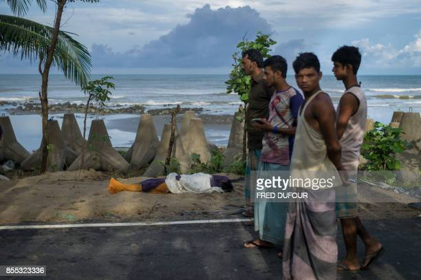 TOPSHOT People stand next to the covered body of Rohingya Muslim refugee near Inani beach Cox's Bazar on September 29 2017 At least 15 people drowned...