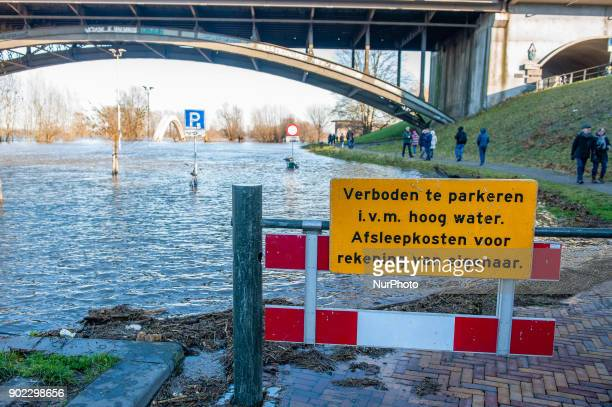 People stand next to the flooded Waal river in Nijmegen The Netherlands on January 7 2018 after heavy rainfalls