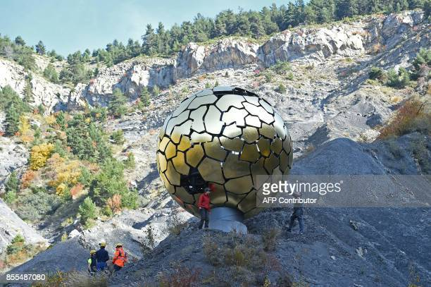 "People stand next to the memorial ""Sonnenkugel"", a sculpture by German artist Jurgen Batscheider, on September 29, 2017 in the French Alps above the..."