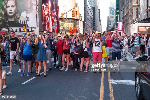 People stand on 42nd Street in Manhattan to photograph Manhattanhenge phenomenon when sun sets in alignment with streets run East to West