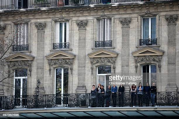 People stand on a balcony as they observe a minutesilence near the Place de la Republique in memory of the victims of the Paris terror attacks last...