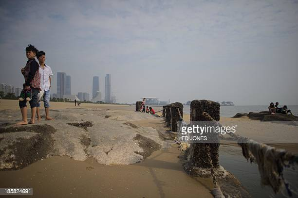 People stand on a beach in Xiamen Fujian province on October 25 2013 China's central bank has unveiled a new regime to allow banks to set a prime...
