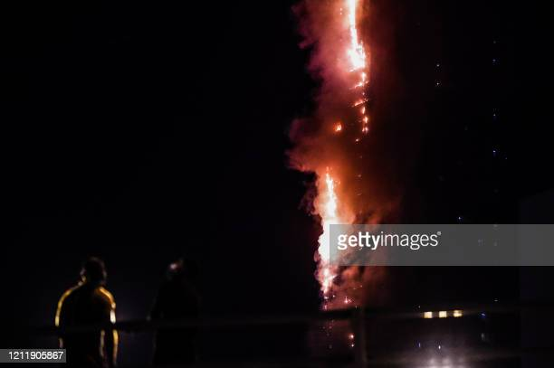 People stand on a bridge and watch a fire that erupted in a 48-storey residential tower in Sharjah in the United Arab Emirates on May 5, 2020.
