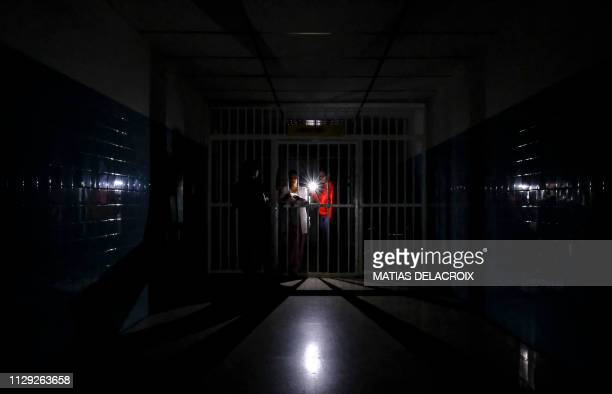 TOPSHOT People stand on a dark corridor at Miguel Perez Carreno hospital in Caracas during the worst power outage in Venezuela's history on March 8...