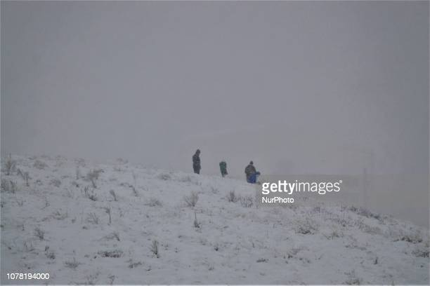 People stand on a hill during a heavy snowfall in the winter season in Ankara Turkey on January 6 2019