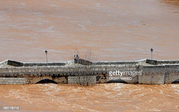 People stand on a medieval bridge over the swollen Pisuerga river in Simancas province of Valladolid on April 1 2013 AFP PHOTO / CESAR MANSO