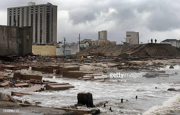 People stand on a mound of construction dirt to view the area where a 2000foot section of the 'uptown' boardwalk was destroyed by flooding from...