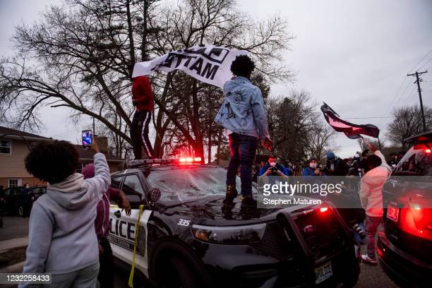 People stand on a police cruiser as protesters take to the streets after Brooklyn Center police shot and killed Daunte Wright during a traffic stop...