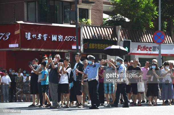 People stand on a road leading to the US Consulate in Chengdu, southwestern China's Sichuan province on July 27, 2020. - The American flag was...