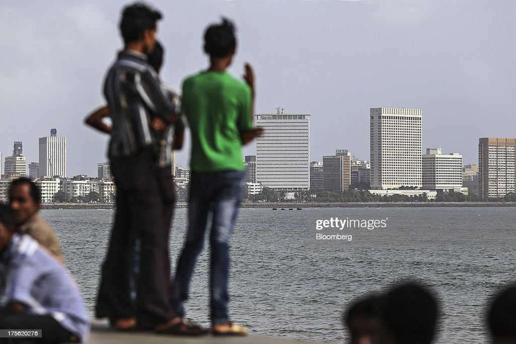 People stand on a sea wall looking out at residential and commercial buildings in the Nariman Point area of Mumbai, India, on Sunday, Aug. 4, 2013. India's purchasing managers index (PMI) for services figures for July are scheduled for release on Aug. 5. Photographer: Dhiraj Singh/Bloomberg via Getty Images