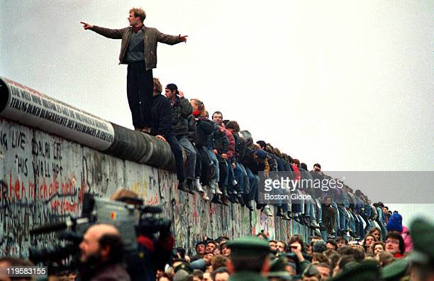 People stand on a section of the Berlin Wall at Potsdamer Platz