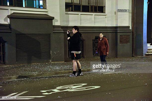 People stand on a street strewn with broken glass from windows in Wellington early on November 14 2016 following an earthquake centred some 90...