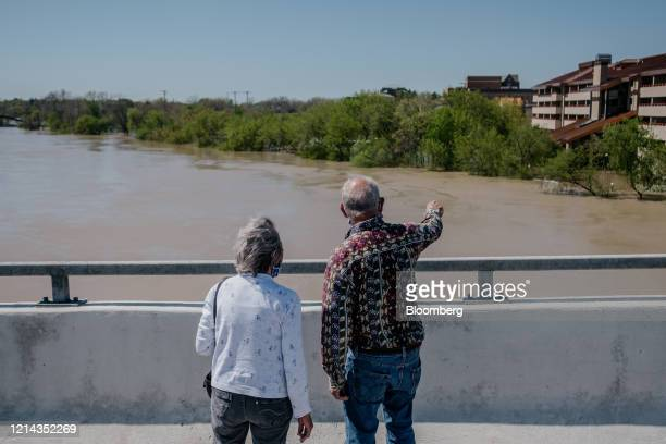 People stand on an overpass over a flooded Tittabawasee River after dams failed in Midland Michigan US on Wednesday May 20 2020 President Donald...