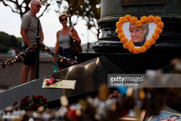 People stand on August 31 2016 at The flame of Liberty replica monument became an unofficial memorial for late Britain's Princess Diana at the Alma...