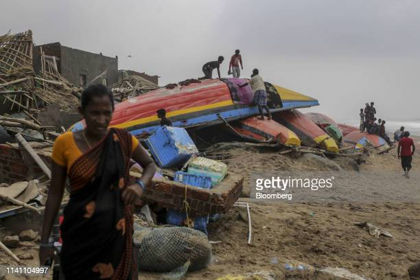 People stand on damaged fishing boats on a beach after Cyclone Fani passes in the Puri district of Odisha India on Saturday May 4 2019 A category 4...
