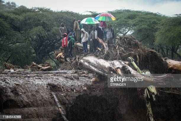 TOPSHOT People stand on debris blocking a highway on a bridge after River Muruny burst its bank following heavy rains in Parua village about 85 km...