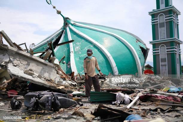 People stand on debris following the earthquake on October 4 2018 in Palu Central Sulawesi Indonesia The death toll from last weeks earthquake and...