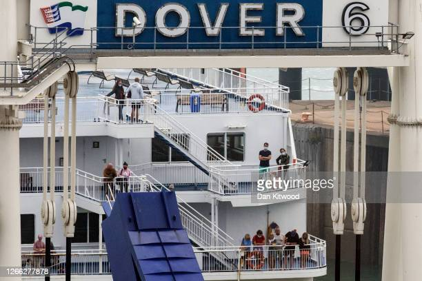 People stand on deck as a ferry returns to Dover port from France on August 14 2020 in Folkestone United Kingdom The UK government citing a rise in...