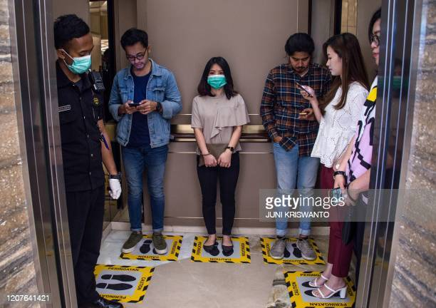 TOPSHOT People stand on designated areas to ensure social distancing inside an elevator at a shopping mall in Surabaya on March 19 amid concerns of...