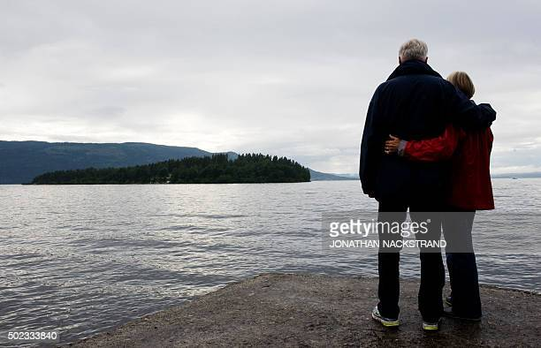 People stand on July 26 2011 on the coast of lake Tyrifjorden infront of Utoeya island in memory of the victims of the July 22 shooting spree at a...