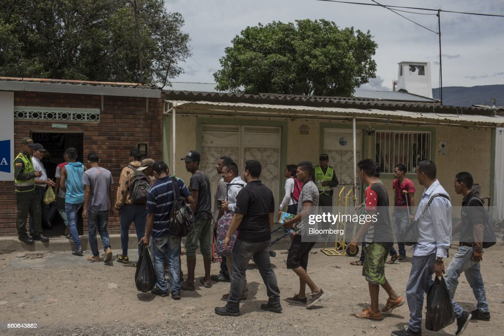 People stand on line for a meal at the Casa de Paso, a church charity offering daily meals and basic medical aid, in Cucuta, Colombia, on Thursday, Sept. 21, 2017. For weeks, Venezuelans have been flocking by the busload to San Antonio del Tachira, a border town of some 62,000 residents, fleeing as President Nicolas Maduro consolidates autocratic power. According to Colombia's migration authority, the number of foreigners entering Cucuta, the first major city across the bridge, more than doubled this summer. Photographer: Nicolo Filippo Rosso/Bloomberg via Getty Images
