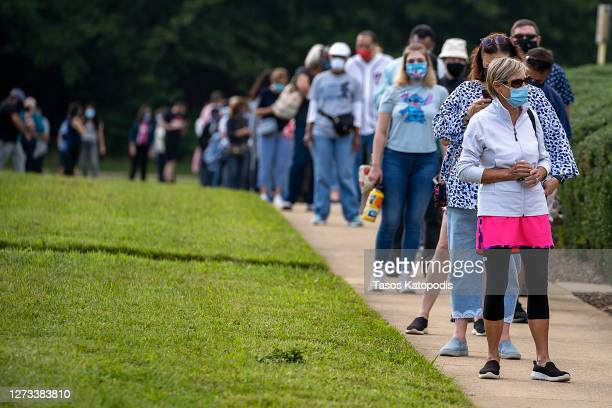 People stand on line, spaced six apart due to COVID-19, in order to vote early at the Fairfax Government Center on September 18, 2020 in Fairfax,...