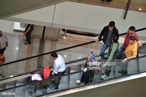 People stand on moving stairs in a shopping mall during the Muslim holy fasting month of Ramadan in Ankara Turkey on May 27 2018