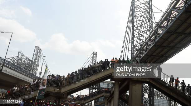 People stand on pedestrian bridge watching Nigerian President Mohammadu Buhari speak during the inauguration of the newly built multistorey mega bus...