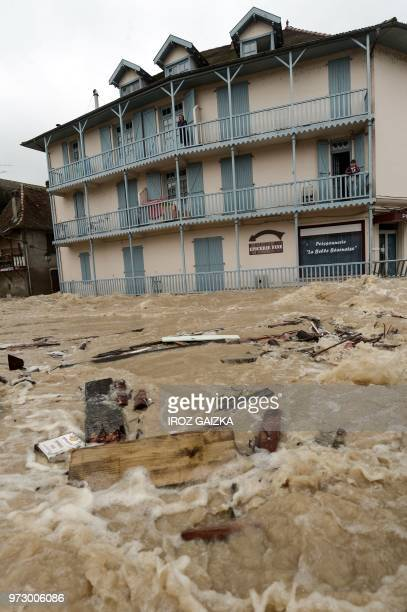 People stand on the balconies of a building watching as flood waters sweep through the streets following heavy rains in SaliesdeBearn south western...