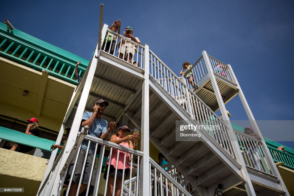 People stand on the balcony and staircase above a pizzeria, one of the only places where cellular reception can be found, after Hurricane Irma in St John, U.S. Virgin Islands, on Tuesday, Sept. 12, 2017. After being struck by Irma last week, the U.S. Virgin Islands couldn't look less like a tourist destination. Many local residents are giving up and getting out after losing everything to the category 5 storm,even as the local authorities in the U.S. territory say they are determined to rebuild the islands. Photographer: Michael Nagle/Bloomberg via Getty Images