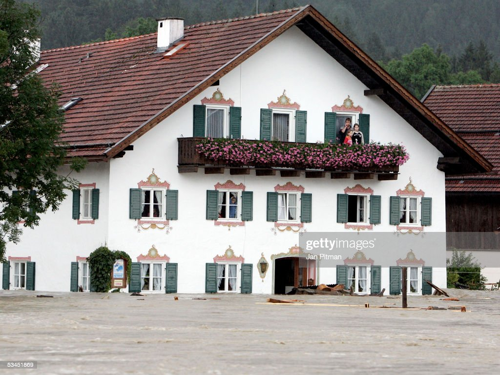People stand on the balcony of their house on August 23, 2005 in Eschenlohe, Germany. The water of many rivers in southern Germany climbed over the banks due to the floods in Austria and Switzerland and heavy rainfalls. Half of the town Eschenlohe is already evacuated, streets in the whole area are closed for traffic.
