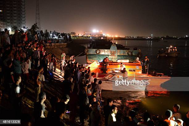 People stand on the bank of the Nile while rescuers search for victims in Cairo Egypt on July 23 2015 At least 21 people including two children were...