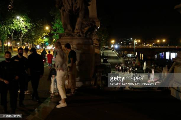 People stand on the banks of the Seine River past the 11pm Covid-19 curfew, early on June 12 after people gathered nearby at Les Invalides for an...