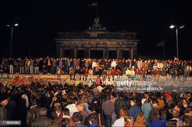 People stand on the Berlin Wall on November 10 1989 in Berlin Germany
