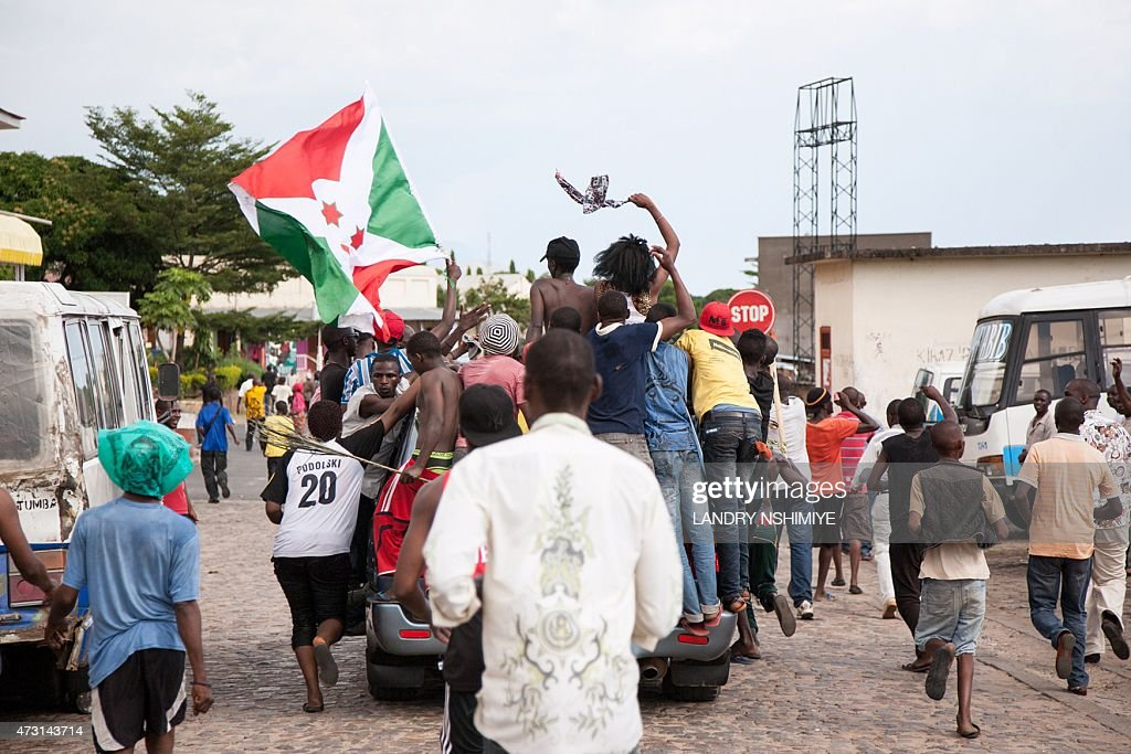 People stand on the bumper of a car as they celebrate in Bujumbura on May 13, 2015 after the announcement of an attempted coup against the Burundian president. A top Burundian general launched a coup attempt against President Pierre Nkurunziza on May 13, after weeks of violent protests against the president's bid to stand for a third term. General Godefroid Niyombare, a powerful former intelligence chief who was sacked earlier in the year, announced via a private radio station that the president had been overthrown hours after he left for neighbouring Tanzania for talks with regional leaders.
